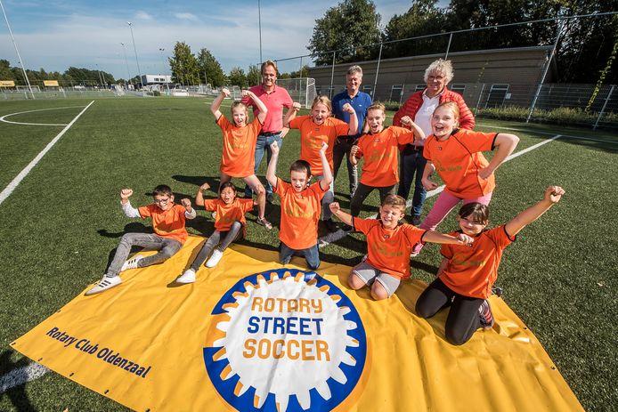 V.l.n.r: Edgar Visscher , Han van Benthem en Martien Boet met enthousiaste leerlingen van Basisschool De Linde. Rotary Streetsoccer speelt zich dit jaar af op kunstgras.