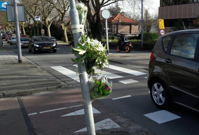 Bij het zebrapad op de Molenlaan in Rotterdam zijn bloemen aan een paal gebonden.