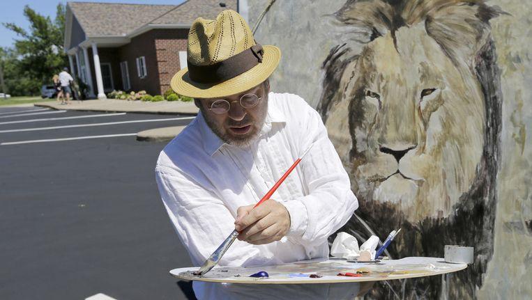 Een man werkt aan een muurschildering van leeuw Cecil op de muur van de praktijk van Walter Palmer.