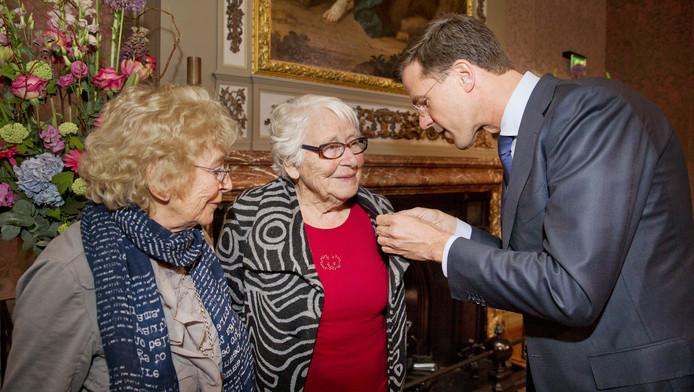 Truus Menger-Oversteegen (M) en Freddie Dekker-Oversteegen, verzetsvriendinnen van Hannie Schaft, kreeg in 2014 het Mobilisatie Oorlogskruis uitgereikt door premier Mark Rutte