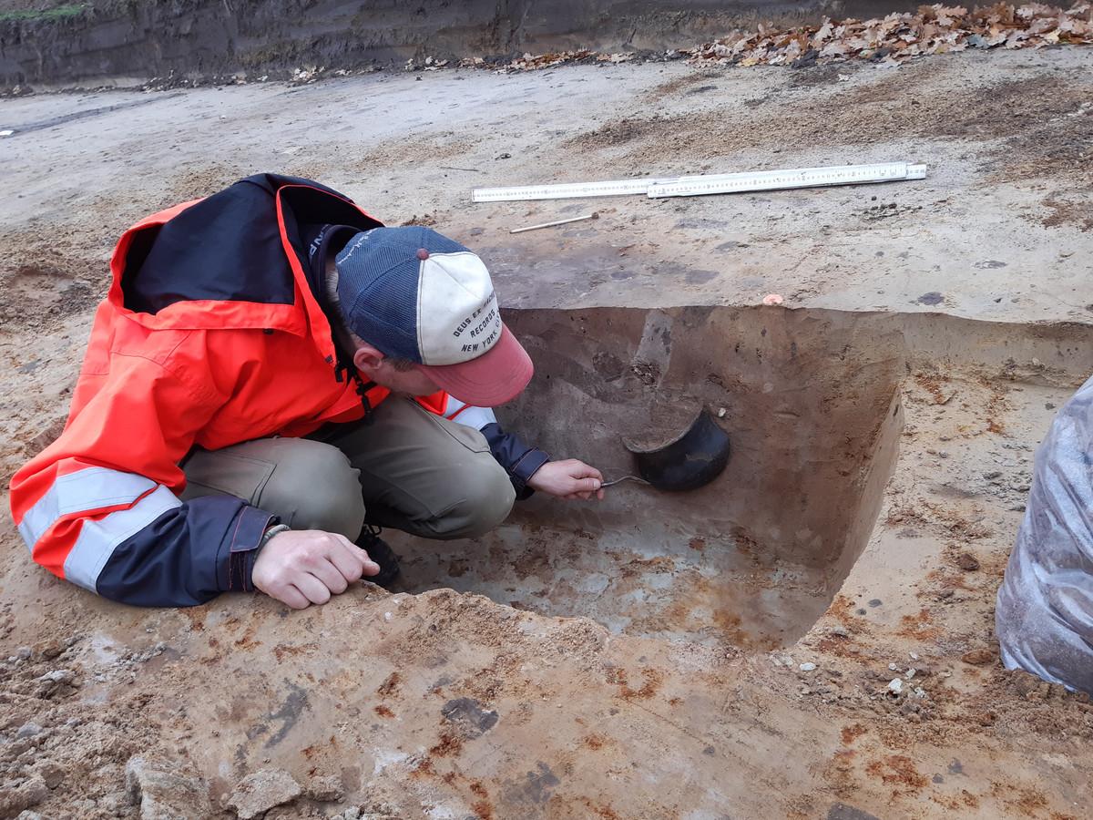 Archeoloog Paul van den Helm onderzoekt een prehistorische grafkuil nabij de Udenhoutseweg. In het spoor van de grafkuil is in profiel een deel van een urn zichtbaar, waarin de crematieresten van een persoon zijn begraven.