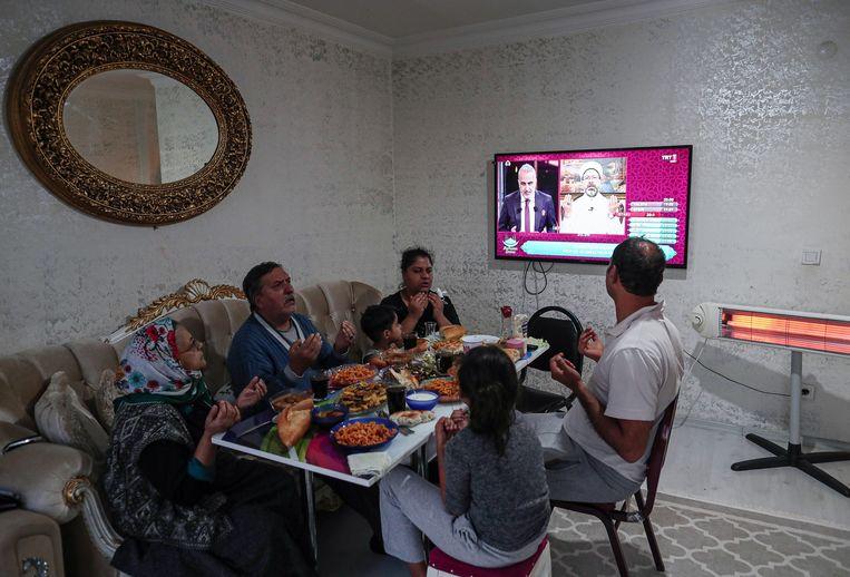 Een Turkse familie bid voor de maaltijd terwijl ze luisteren naar Erbas preek bij het begin van de ramadan. Beeld EPA