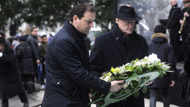 Vice-premier en minister van Sociale Zaken en Werkgelegenheid Lodewijk Asscher (L) en staatssecretaris Martin van Rijn van Volksgezondheid leggen een krans op het spiegelmonument Nooit Meer Auschwitz in het Wertheimpark waar wordt herdacht dat het 70 jaar geleden is dat concentratiekampen Auschwitz en Birkenau op 27 januari 1945 werden bevrijd. Beeld anp
