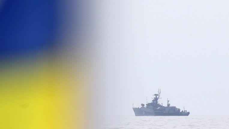 Een Oekraïnse vlag wappert, op de Zwarte Zee is een Russische patrouilleboot te zien Beeld epa