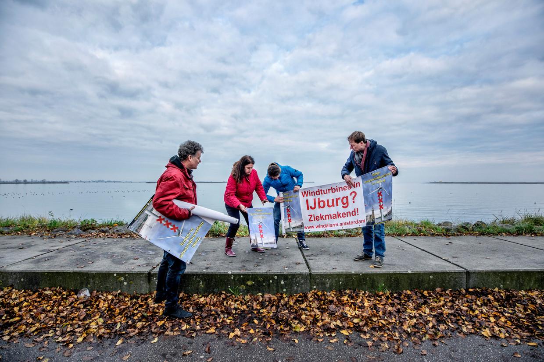 Actievoerders van Windalarm Amsterdam rollen op IJburg hun spandoeken uit bij de plek waar de windmolens moeten komen. Beeld Raymond Rutting / de Volkskrant
