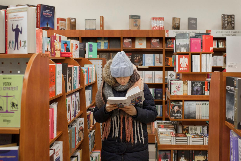 Een jonge vrouw leest een boek in een boekhandel in Kiev. Door eeuwenlange Russische invloed is het aanbod van Oekraïenstalige cultuur beperkt. Beeld Emile Ducke