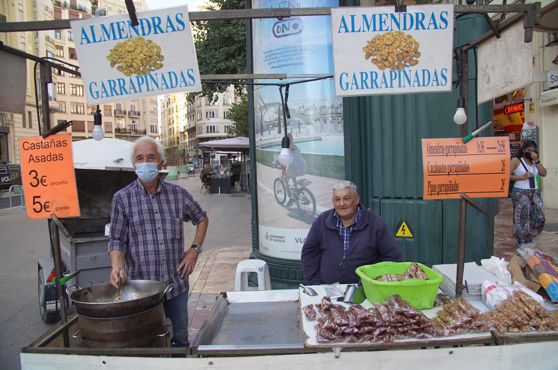 Voormalig stierenvechter Pedro José Beneit (l), die gesuikerde pinda's verkoopt voor het stadhuis van Valencia.