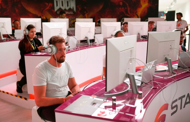 Bezoekers van videogamebeurs Gamescom spelen de game 'Doom' op de stand van Stadia. Moederbedrijf Google heeft ondertussen de ambities voor zijn videogamemerk flink naar beneden bijgesteld. Beeld AFP
