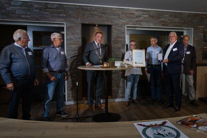 Het Rijssense Eendracht bestaat 100 jaar en wordt daarom koninklijk onderscheiden. Loco-burgemeester Beens reikt de erepenning uit.