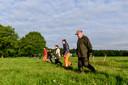 Jan Vos (voorgrond) leidt een groep van zo'n dertig vrijwilligers die in linie de weilanden aflopen op reekalfjes.
