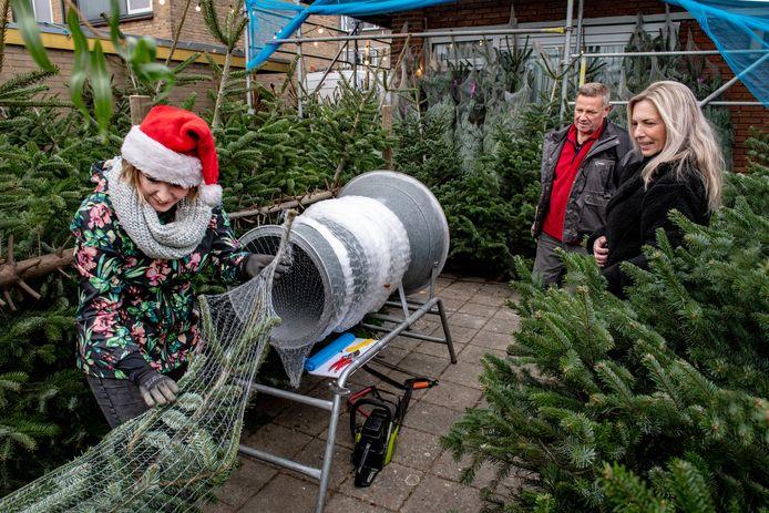 Irma Vissers (rechts) en Frans Litjes kijken toe hoe Jeanet Litjes een kerstboom inpakt.