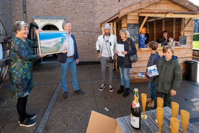 Bestuursvoorzitter Margreet van Gastel en directeur Jos van den Mosselaar houden het cadeau voor de familie Ghanem omhoog: een foto op linnen, kunstwerk van Van Gastel die momenteel in het museum met haar fotodoeken exposeert.