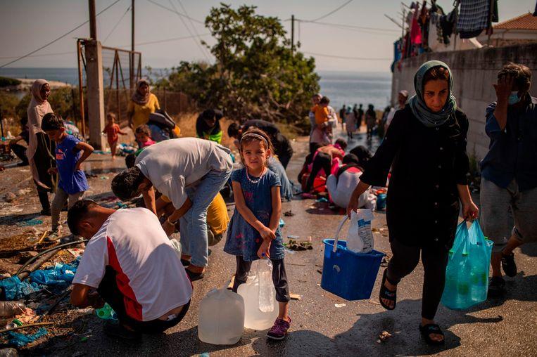 Een meisje wacht tot ze haar jerrycans met water kan vullen, vlakbij een tijdelijk kamp dat is opgezet nadat Moria in vlammen opging.  Beeld AFP
