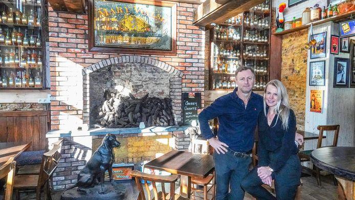 Zaakvoerster Caroline Foley en haar partner Justin Bedford, in de kroeg. Op de achtergrond zie je de muur met flessen in. Waarop de namen van de gesneuvelde Ieren staan.