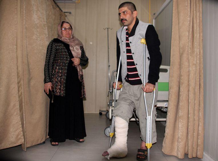 Een slachtoffer van de aardbeving wordt geholpen in het ziekenhuis van Sulaimaniya in Irak.  Beeld AFP
