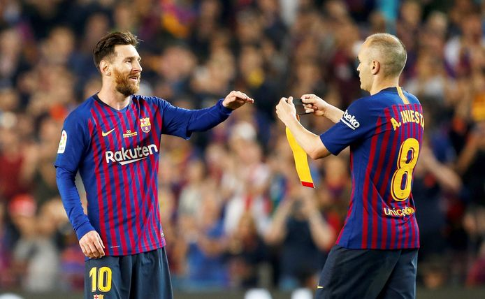 Andrés Iniesta geeft de aanvoerdersband door aan Lionel Messi.