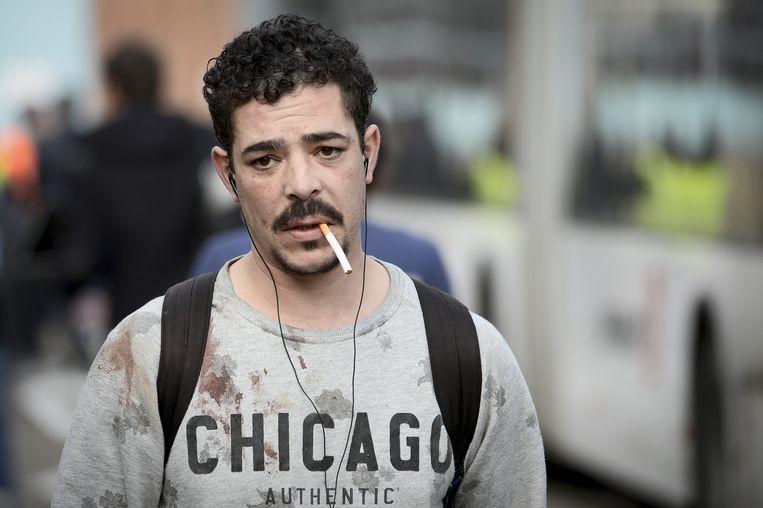 Een man met bebloed shirt bij de Brusselse luchthaven. Beeld belga