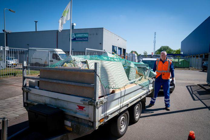 Medewerker Bert Rensen van afvalbrengstation Arnhem-Zuid inspecteert een met grofvuil beladen aanhanger.