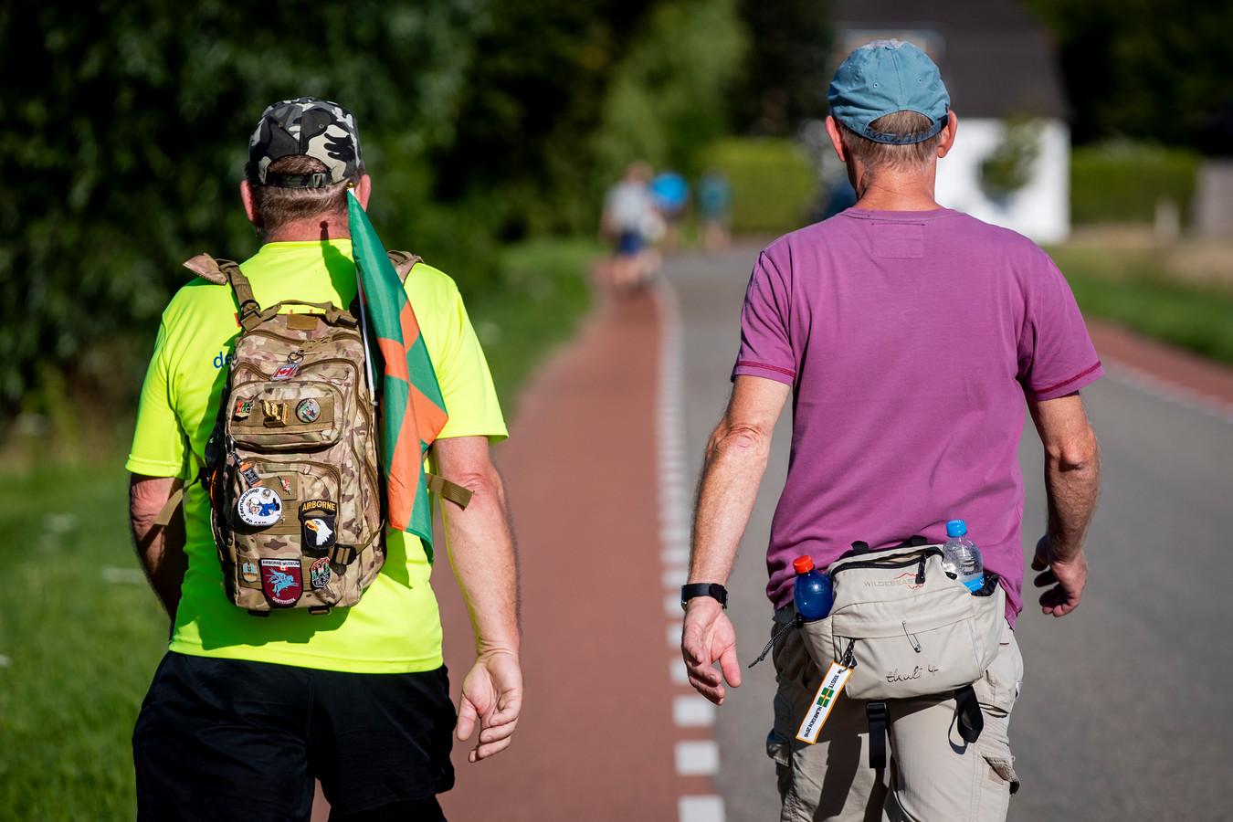 Deelnemers aan de Alternatieve Vierdaagse dragen een vlag van de Nijmeegse Vierdaagse bij zich op de dag dat de 104e editie van start had moeten gaan.