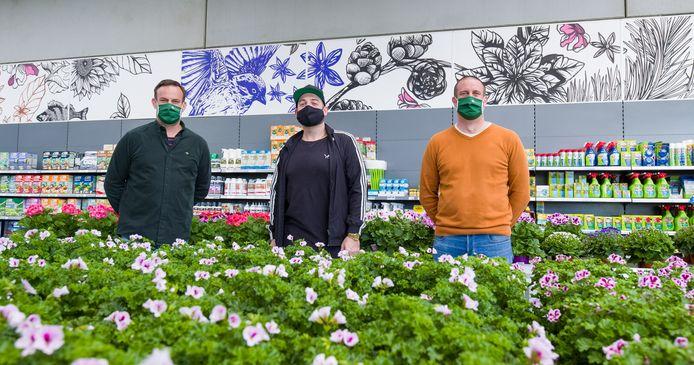 Jan Sampermans (links), kunstenaar Tom Herck (midden) en Tom Sampermans (rechts) tonen de gloednieuwe illustratiewerken boven de producten van het tuincentrum.