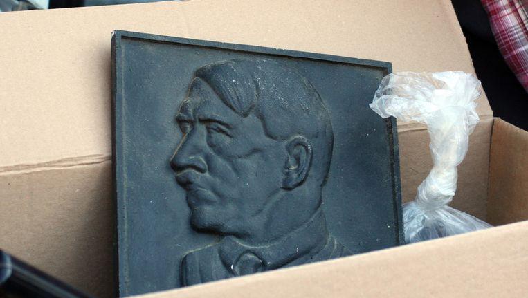 Een portret van Hitler tussen in beslag genomen spullen na een huiszoeking bij vermoedelijke neonazi's in Juelich, vandaag. Beeld ap