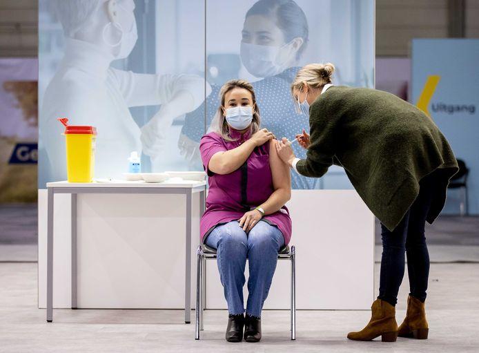 Sanna Elkadiri, medewerkster van verpleeghuis Het Wereldhuis, krijgt het eerste vaccin. Verleners van acute zorg, zoals ambulancepersoneel en IC-medewerkers worden in diverse ziekenhuizen geprikt tegen het coronavirus. ANP ROBIN VAN LONKHUIJSEN