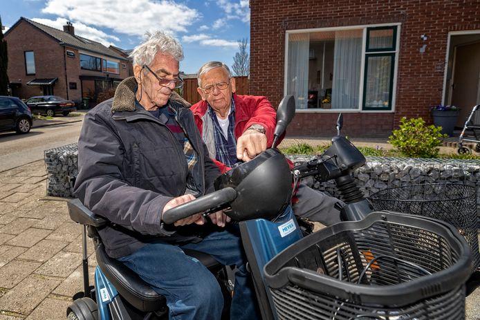 Cor de Jong (78) (r.) instrueert Cees de Langen (77) hoe om te gaan met zijn scootmobiel.