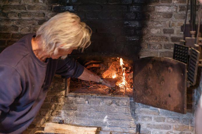 Hans Hanssen laat zien hoe vroeger vuur werd gemaakt, en zorgt dat de oven van vuur wordt voorzien.