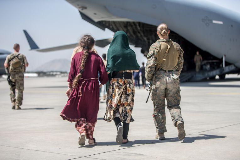 Een Amerikaanse marinier loopt over het vliegveld in Kaboel met twee kinderen op weg naar een vliegtuig, het land uit.   Beeld EPA
