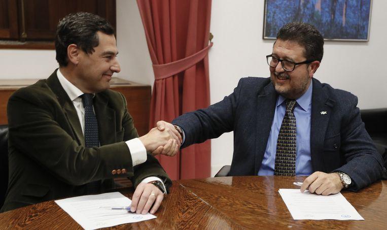Juan Manuel Moreno van de Volkspartij schudt de hand van Francisco Serrano van het extreem-rechtse Vox tijdens een bijeenkomst in Sevilla begin dit jaar. Beeld Jose Manuel Vidal / EPA
