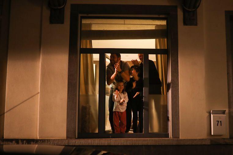Een familie in Brussel klapt vanuit huis voor de mensen die werken in de verpleging.  Beeld AP
