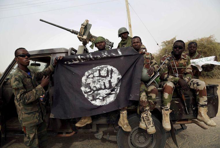 Nigeriaanse soldaten houden een buitgemaakte vlag van Boko Haram vast.  Beeld REUTERS