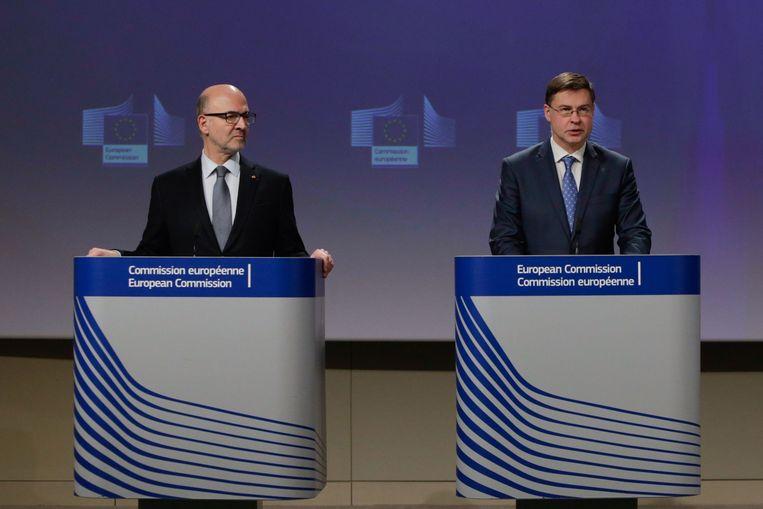 De EU-commissarissen Pierre Moscovici (l.) en Valdis Dombrovskis gaven woensdag in Brussel nadere uitleg over de noodmaatregelen.  Beeld AFP