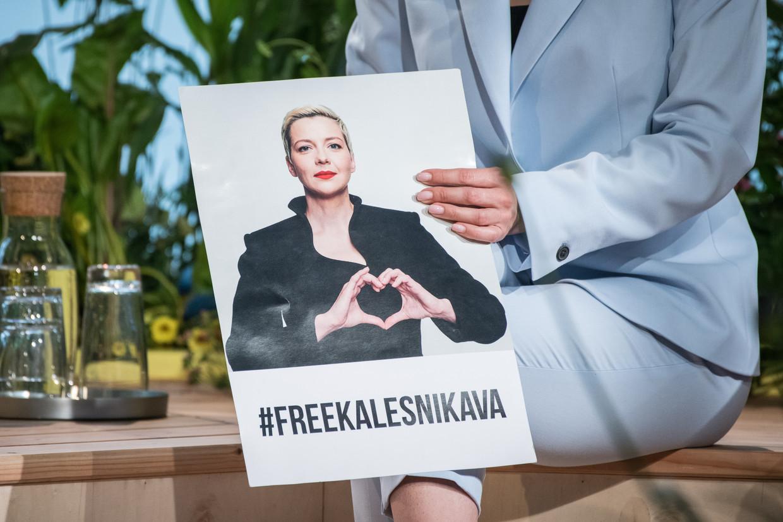 De zus van politiek gevangene Maria Kolesnikova houdt een protestbord met haar beeltenis vast.