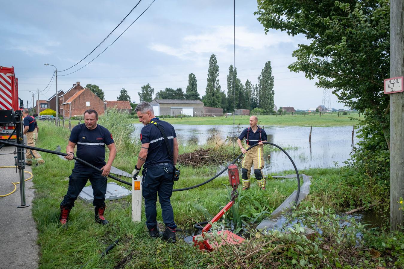 De brandweer pompt water uit een veld en een beek weg in de Tiendenschuurstraat.
