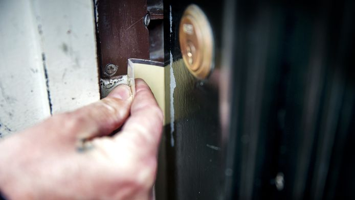 Ter illustratie. Een inbreker opent met een pasje of een stuk plastic een voordeur (flipperen).