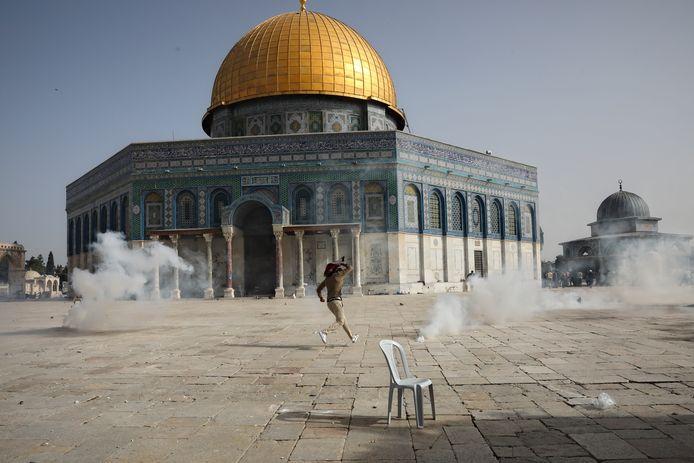 Een Palestijnse man rent tussen de traangasgranaten weg bij de al-Aqsa-moskeeman.