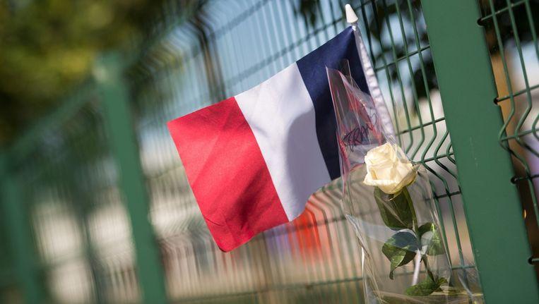 Een Franse vlag en een witte roos hangen aan het hek van de fabriek van Air Products, waar vrijdag een man werd onthoofd. Beeld EPA