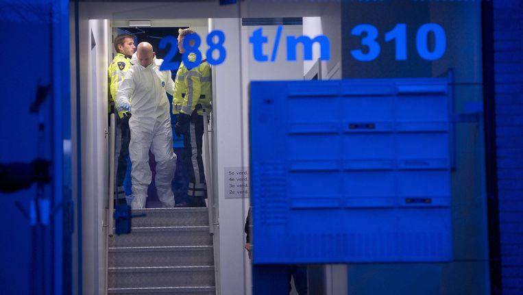 Agenten en forensisch medewerkers van de politie aan het werk in de portiek Beeld anp