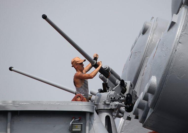 Een Russische marinier maakt de geweren van oorlogsschip Admiraal Vinogradov schoon. Het schip botste vrijdag bijna met het Amerikaanse schip USS Chancellorsville.  Beeld AP