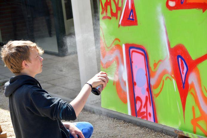 Niobe (13 jaar) is zeer geconcentreerd aan het werk. Sinds een jaar is hij bezig met graffiti, een autodidact, en nu hij de kans heeft tijdens het kunstevenement in Hulst kan hij niet meer stoppen.