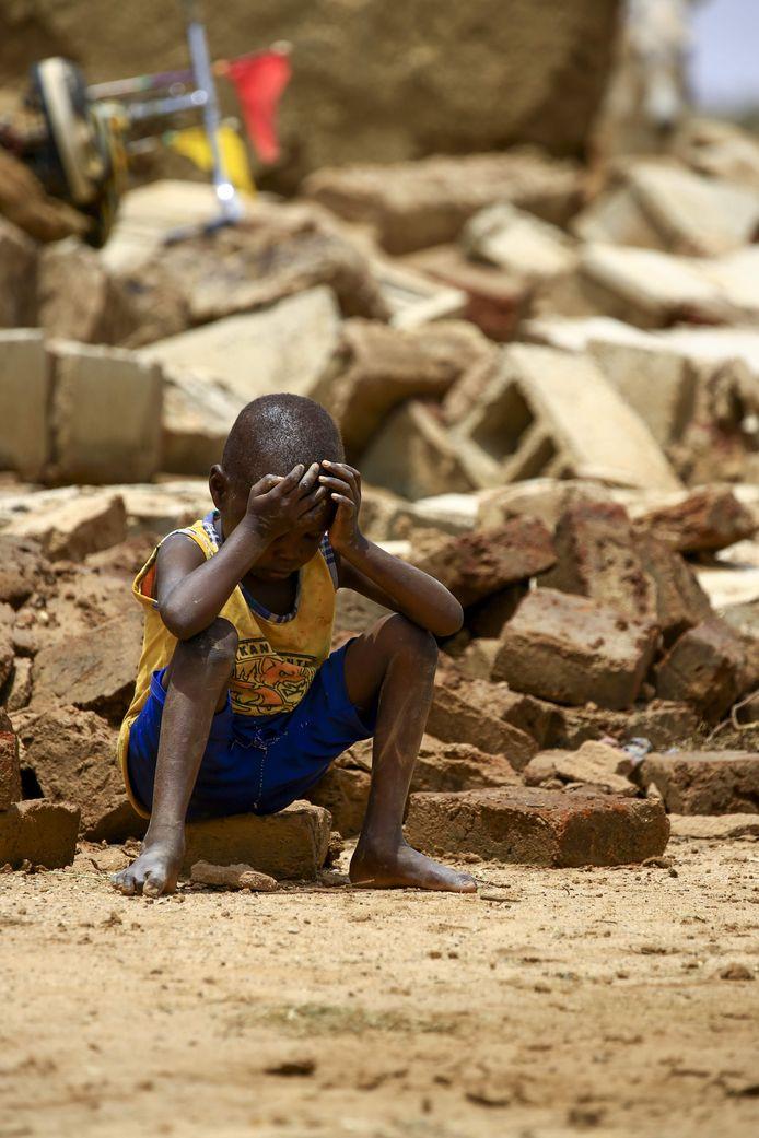 Een Soedanese jongen zit op het puin van een huis, dat instortte door overstromingen en stortregens.