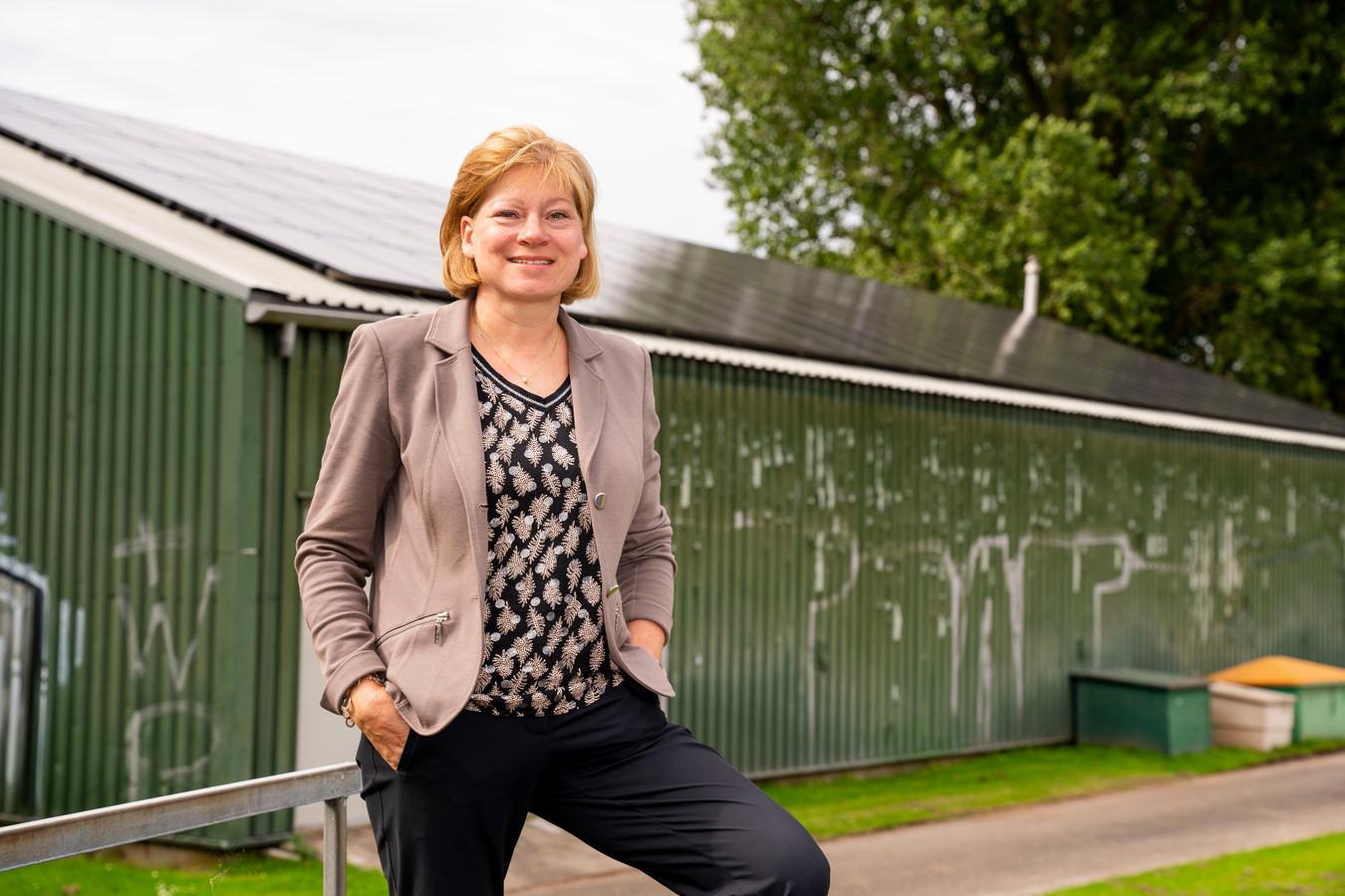 Jacqueline van Dongen bij de Honk- en Softbalvereniging Zwijndrecht, met op het dak 88 zonnepanelen.