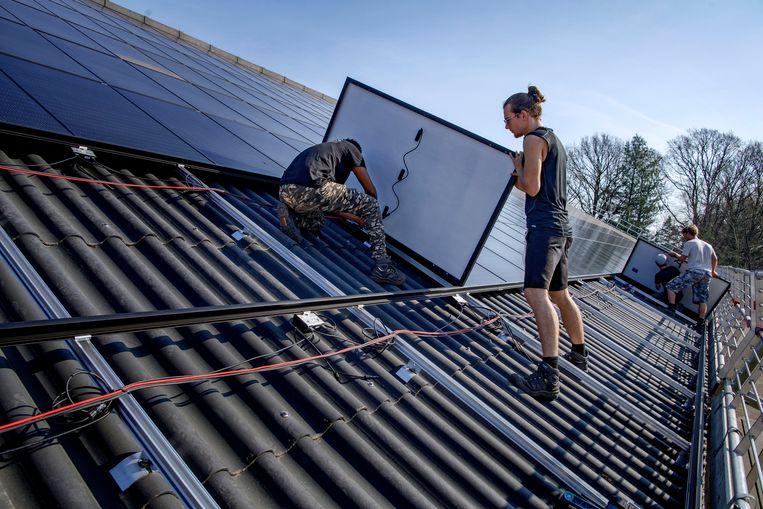 Op het dak van een stal van een boerderij worden zonnepanelen gelegd die stroom moeten opwekken om zo het bedrijf te verduurzamen. Beeld Hollandse Hoogte / Dolph Cantrijn