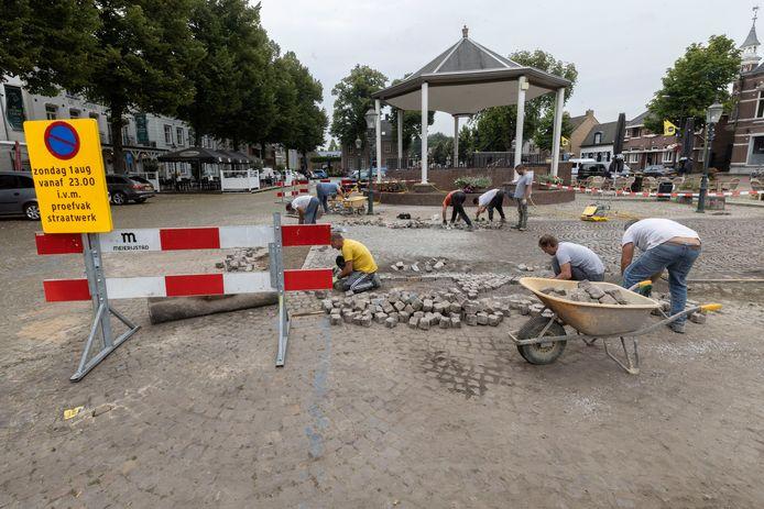 Proefvak herbestrating Markt, stratenmakers aan het werk.