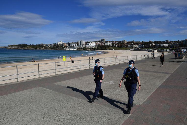 De politie patrouilleert op Bondi Beach in Sydney, Australia. Mensen mogen hun huis alleen uit voor essentiële bezigheden als boodschappen en sport. Beeld EPA