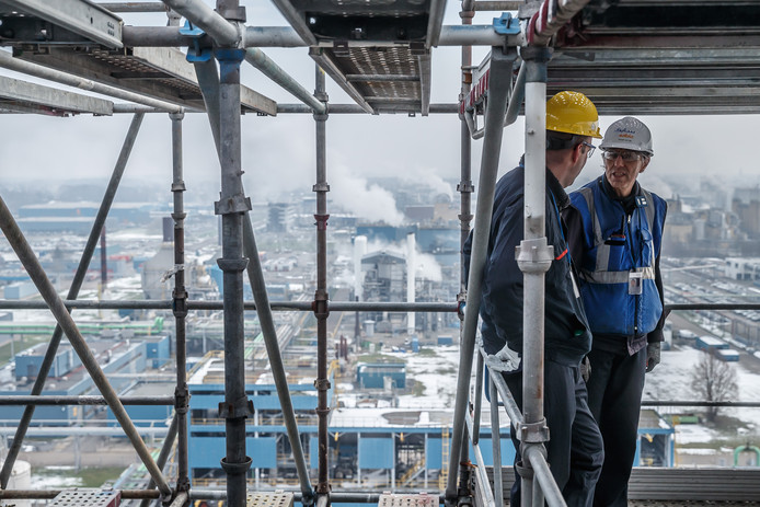 Ronald van Zijp van Sabic (witte helm) geeft op de 48 meter hoge steiger rond de destillatiekolommen van de PPE-fabriek in Bergen op Zoom uitleg over de heringebruikname van de productielijn.