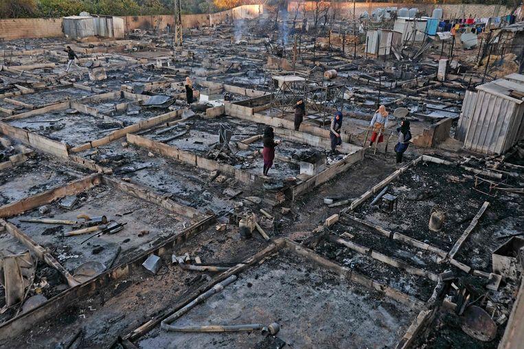 Syrische vluchtelingen redden bezittingen uit de resten van hun onderkomens in een kamp dat 's nachts in brand is gestoken in de Noord-Libanese stad Bhanine op 27 december 2020, na een gevecht tussen leden van het kamp en een lokale Libanese familie. Beeld AFP