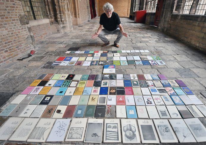 Ko de Jonge met alle 154 nummers die in de Slibreeks verschenen. Hij heeft ze uitgespreid in de Kloostergang van het Middelburgse abdijcomplex, waar de Slibreeks in de toenmalige Provinciale Bibliotheek ontstond.