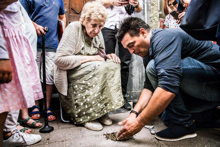 Tony Weber-Susskind (91) kijkt toe terwijl iemand de gedenksteen in de stoep verwerkt. Beeld Aurélie Geurts